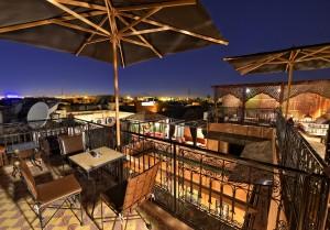 Dachterasse im Riad La Maison Nomade in Marrakesch mit Sonnenschirmen und Ausblick über die Altstadt