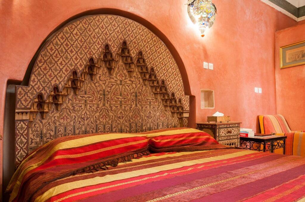 Das Doppelbett mit aufwändiger Holzschnitzerei und rotem Tadelakt an allen Wänden