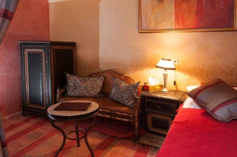 Zimmer Tawarget im Hotel in Marrakesch mit Sitzbank, Tisch, Doppelbett und integriertem Duschbereich mit WC