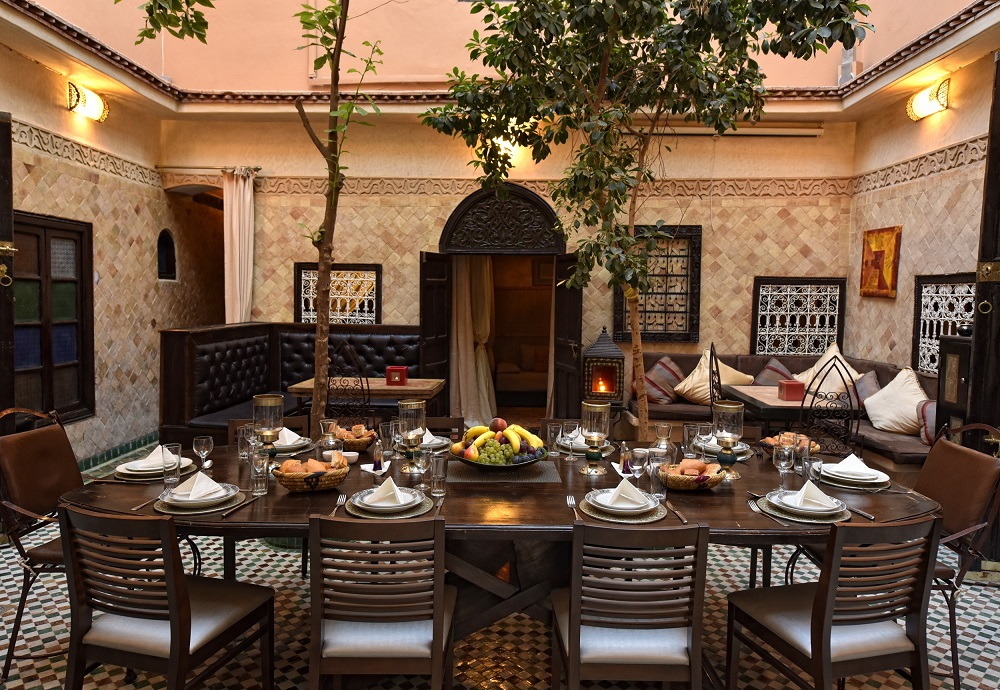 Patio des Riad La Maison Nomade ab 2016 mit großem Tisch in der Mitte und Bänken in den Ecken