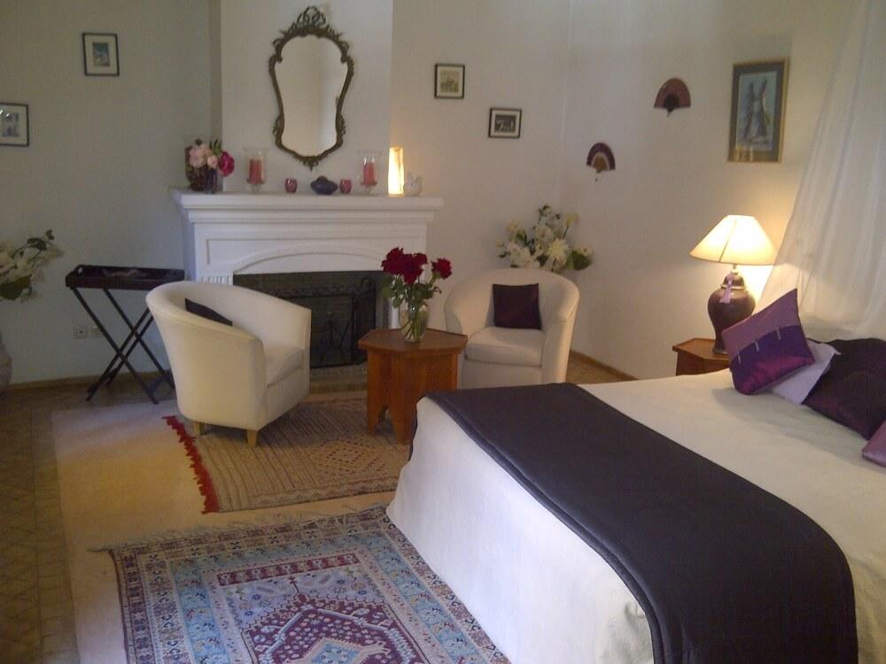 Salon mit Doppelbett und Kamin im Riad La Maison Nomade