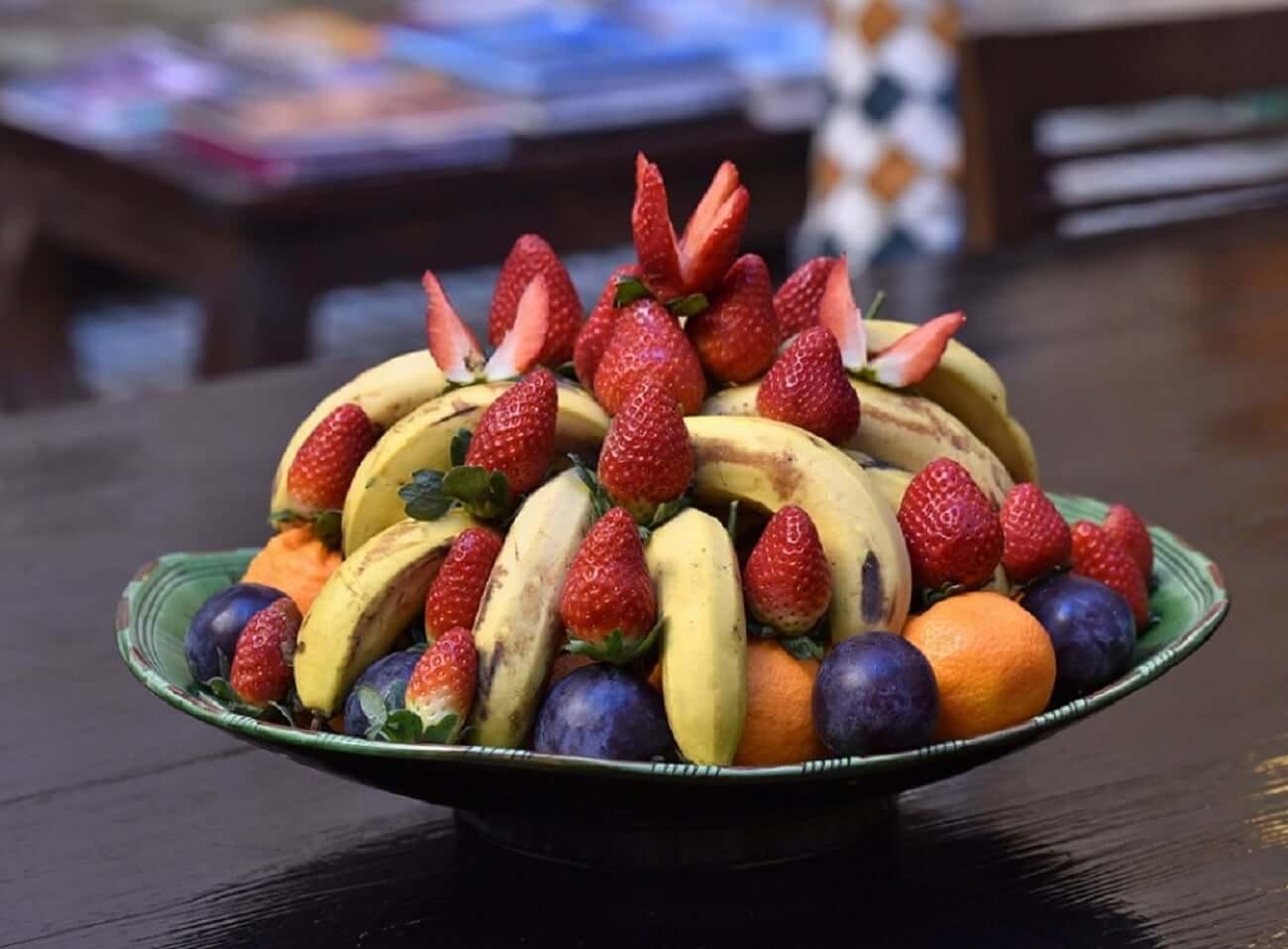 Obstteller mit Bananen, Orangen, Pflaumen und Erdbeeren