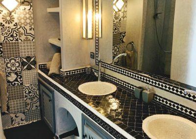 Bad mit zwei Waschbecken aus schwarzen und weißen Mosaikfliesen